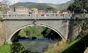 Ponte Gregoriano över floden Arienes. Louis Jean Desprez bör ha stått vid det som i dag är brons högra fäste då han målade vyn över Tivoli. Bredvd ligger ett parkeringshus i gult tegel.